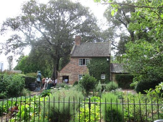 Small redbrick cottage hidden amongst trees and garden