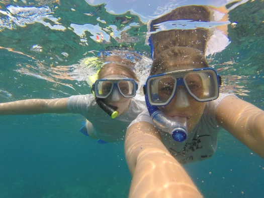 Snorkel seflie using a GoPro while snorkelling with reef sharks in the clear ocean water of Fiji
