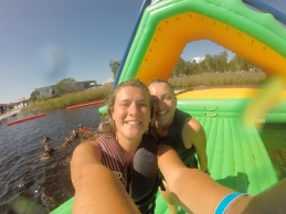 Girls take a seflie on an inflatable challenge during a sunny day