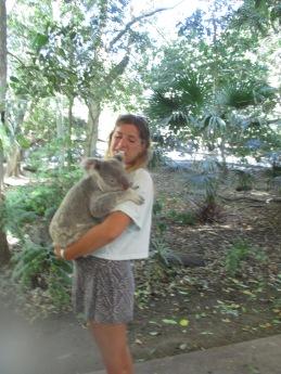 Girl holding a koala in a forest setting of Australia