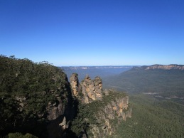 The Three Sisters rock formations as part of the Blue Mountains in Sydney, Australia - surrounded by lush green forest and flat mountains stretching into the blue horizon