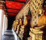 Golden buddha shrines line the outside edges of a temple