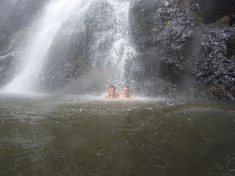 Girls smile as they sit beneath a rushing waterfall