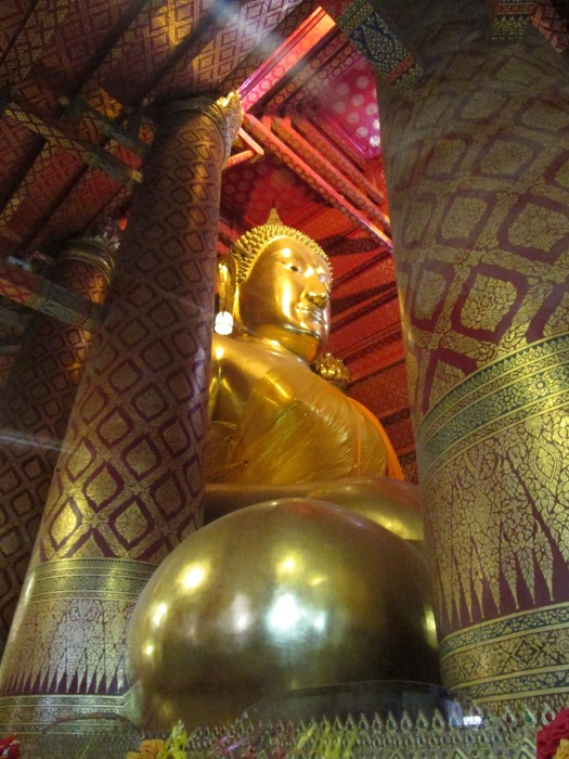 A large golden buddha sits nestled among tall and intricately decorated pillars