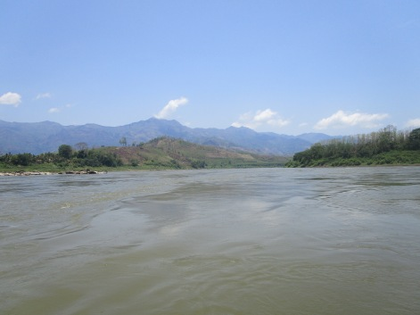 Thai hills in the distance as a boat sails down the Mekong River