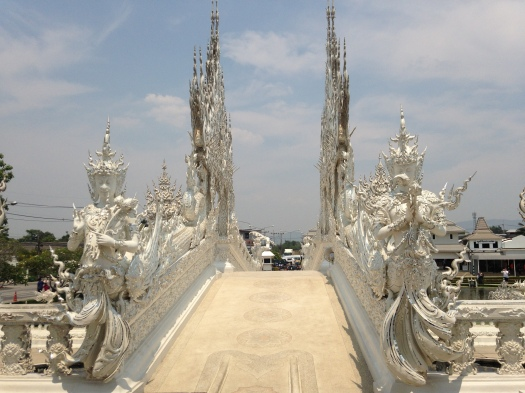 Temple bridge entrance flanked by imposing white statues
