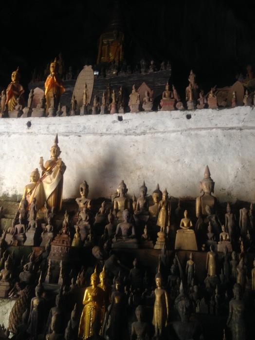 Golden and wooden statues piled around inside a Buddha Cave near Luang Prabang, Laos