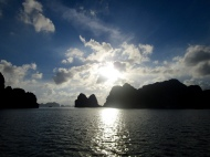 The sun casts a silhouette of the mountains and reflect the ocean in Halong Bay