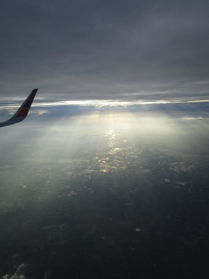 Sunlight peeks through the clouds during a flight over a city
