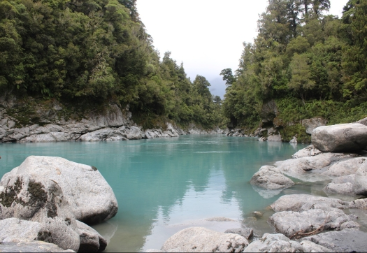 The dazzling blue waters fill Hokitika Gorge with green forest on either side and grey rocks in the foreground