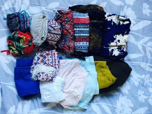 Summer outfits and women's clothing folded neatly.