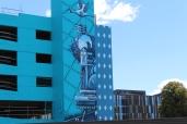 Blue cartoon street art on the side on derelict car park