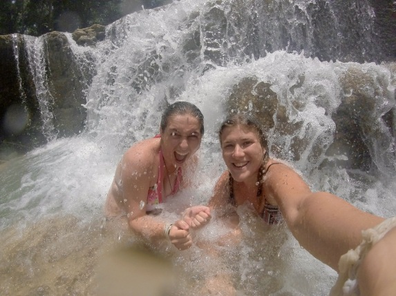 Girls smile as they sit beneath a waterfall