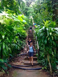 Descending the steps from the top of a waterfall through thick jungle