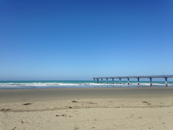 A pier extends into the sea from the beach on a cloudless day