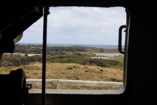 View from inside a gun at a battery on a hill overlooking grass and