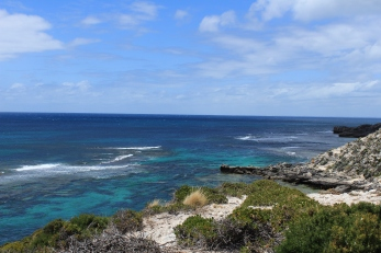 Rocky cliff edge overlooks turquoise sea