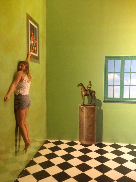Girl pretends to hold onto wall painting at Art in Paradise Chiang Mai