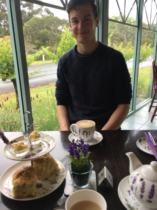 Man smiles at camera with scones and lavender tea
